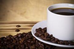 Kaffeebohnen und Kaffee in der weißen Schale auf Holztisch gegenüber von a Lizenzfreies Stockfoto