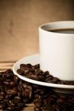 Kaffeebohnen und Kaffee in der weißen Schale auf Holztisch gegenüber von a Lizenzfreie Stockfotos