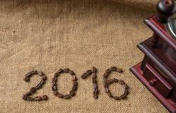 Kaffeebohnen und Kaffeemühle, Abschluss oben auf dem Hintergrund des Leinwandsacks, 2016 guten Rutsch ins Neue Jahr Lizenzfreies Stockbild