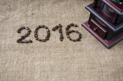 Kaffeebohnen und Kaffeemühle, Abschluss oben auf dem Hintergrund des Leinwandsacks, 2016 guten Rutsch ins Neue Jahr Stockfotografie