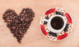 Kaffeebohnen und Kaffeetasse auf dem Tisch Stockfotos