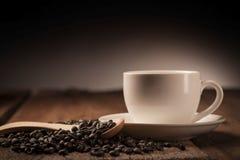Kaffeebohnen und Kaffeetasse auf Holz lizenzfreie stockbilder
