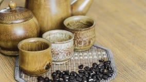 Kaffeebohnen und Kaffeetassen stellten auf hölzernen Hintergrund ein Abbildung der roten Lilie (Weichzeichnung) Lizenzfreies Stockbild