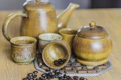 Kaffeebohnen und Kaffeetassen stellten auf hölzernen Hintergrund ein Abbildung der roten Lilie (Weichzeichnung) Lizenzfreie Stockfotos