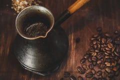 Kaffeebohnen und Metallschaufel auf hölzernem Hintergrund Lizenzfreie Stockfotos