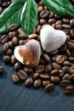 Kaffeebohnen und Pralinen in einem Herzen formen Stockfoto