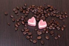 Kaffeebohnen und Süßigkeiten in einem Herzen formen auf dunklen Hintergrund Lizenzfreie Stockfotos