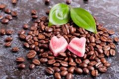 Kaffeebohnen und Süßigkeiten in einem Herzen formen auf dunklen Hintergrund Stockfotos