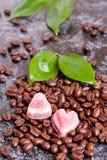 Kaffeebohnen und Süßigkeiten in einem Herzen formen auf dunklen Hintergrund Stockbilder
