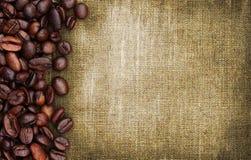 Kaffeebohnen und Sackhintergrund Stockbilder