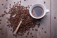 Kaffeebohnen und weißes Cup auf hölzernem Hintergrund Stockbild