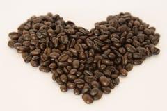 Kaffeebohnen vereinbarten in einer Herzform auf weißem Hintergrund Stockbilder