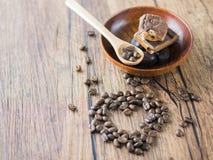 Kaffeebohnen vereinbarten Herzzahl mit Löffel und Schokoriegeln Lizenzfreie Stockbilder