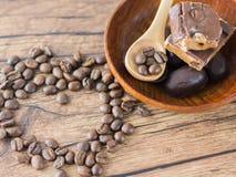 Kaffeebohnen vereinbarten Herzzahl mit Löffel und Schokoriegeln Stockfoto
