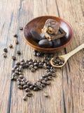 Kaffeebohnen vereinbarten Herzzahl mit Löffel und Schokoriegeln Lizenzfreie Stockfotografie