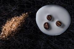 Kaffeebohnen in verschütteter Milch und in braunem Zucker auf einem Schwarzen und einem Silberhintergrund, zurückhaltend Stockfoto