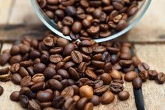 Kaffeebohnen zerbröckelt auf einem hölzernen Hintergrund Lizenzfreie Stockbilder