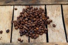 Kaffeebohnen zerstreut auf hölzerne Bretter Lizenzfreie Stockbilder