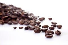 Kaffeebohnen zerstreut und auf einem weißen Hintergrund lokalisiert Stockfoto