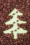Kaffeebohnen zerstreuten auf Grünbuch mit gezogenem Weihnachtsbaum Stockbilder