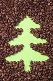 Kaffeebohnen zerstreuten auf Grünbuch mit gezogenem Weihnachtsbaum Lizenzfreie Stockbilder