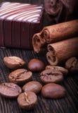 Kaffeebohnen, Zimtstangen und Schokolade auf hölzernem Hintergrund Lizenzfreie Stockfotos