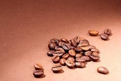 Kaffeebohnenahaufnahme auf einem braunen Hintergrund Lizenzfreie Stockfotos