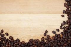 Kaffeebohnerand auf hölzernem Schreibtisch Lizenzfreie Stockfotos