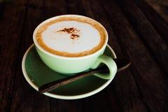 Kaffeecappuccino in einer grünen Schale auf Untertasse steht auf hölzernem Couchtisch Lizenzfreies Stockbild