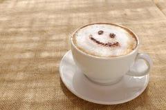 Kaffeecappuccino mit lächelndem willkommenem glücklichem Gesicht des Schaums oder der Schokolade stockbild