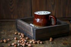 Kaffeeeibisch und -nüsse auf einem hölzernen braunen Hintergrund, geschmackvoll und gemütlich lizenzfreie stockfotos