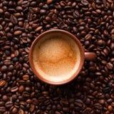 Kaffeeespresso auf Kaffeebohnen lizenzfreies stockbild