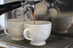 Kaffeeespresso, der in 2 weiße Schalen gießt stockfotos