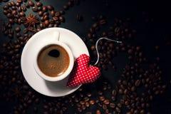 Kaffeeespresso mit Kaffeebohnen auf einem Hintergrund und einem roten Plüsch Lizenzfreies Stockfoto
