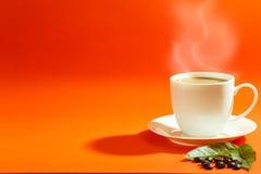 Kaffeegetränk in der weißen Kaffeetasse und schwarze Kaffeebohnen und Rückseite Stockfotos