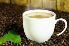 Kaffeegetränk in der weißen Kaffeetasse und schwarze Kaffeebohnen und Rückseite Stockfoto