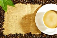 Kaffeegetränk in der weißen Kaffeetasse und schwarze Kaffeebohnen und Rückseite Stockfotografie
