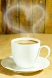 Kaffeegetränk in der weißen Kaffeetasse und schwarze Kaffeebohnen und Rückseite Lizenzfreie Stockfotos