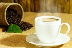 Kaffeegetränk in der weißen Kaffeetasse und schwarze Kaffeebohnen und Rückseite Stockbild