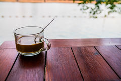 Kaffeeglas auf Holztisch mit Flusshintergrund Stockfotografie