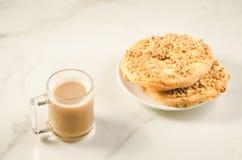 Kaffeeglas mit frischem trockenem Keks zwei mit Nuss/Coffee-Glas mit frischem trockenem Keks zwei mit Nüssen auf einem weißen Mar stockbilder