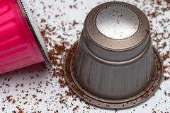 Kaffeehülsenkapseln auf dem weißen Hintergrund gestreut mit gemahlenem Kaffee Stockbilder