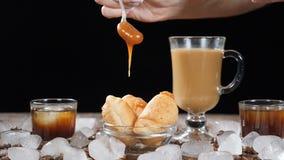 Kaffeehaus mit köstlichen Hörnchen auf Glasplatte Heißes klares flüssiges Karamell, das unten auf Nachtisch in der Zeitlupe auslä stock footage