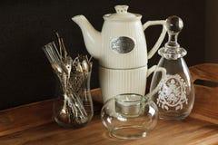 Kaffeekanne, Löffel, Kerze und Vase lizenzfreie stockfotografie