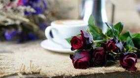 Kaffeeliebe mit Rosen auf Milch, Lattekaffeekunst Stockbilder