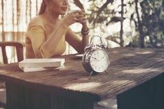 Kaffeemädchen, das im Garten sich entspannt stockfotografie