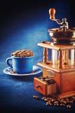 Kaffeemühle mit Bohnen und Schale auf der Untertasse, die auf blauem Vorsprung steht Stockfotografie