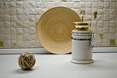 Kaffeemühle mit hölzerner Platte und dekorativem Strohbereich Stockbild