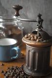 Kaffeemühle mit Kaffeebohnen und unscharfer Schale in der Tabelle Lizenzfreie Stockfotos