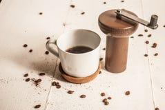 Kaffeemühle mit Schale schwarzem Kaffee Lizenzfreies Stockbild